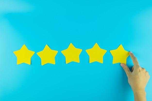 Cliente che tiene una nota di carta gialla a cinque stelle su fondo blu. recensioni dei clienti, feedback, valutazione, classificazione e concetto di servizio.