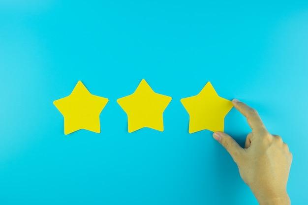 Cliente che tiene una nota di carta gialla a tre stelle su fondo blu. recensioni dei clienti, feedback, valutazione, classificazione e concetto di servizio.