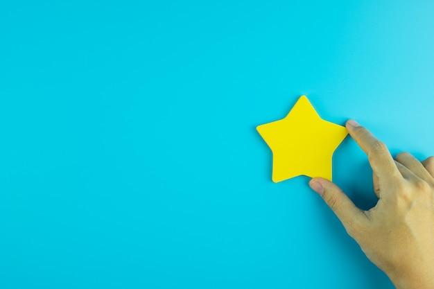 Cliente che tiene una nota di carta gialla della stella su fondo blu. recensioni dei clienti, feedback, valutazione, classificazione e concetto di servizio.