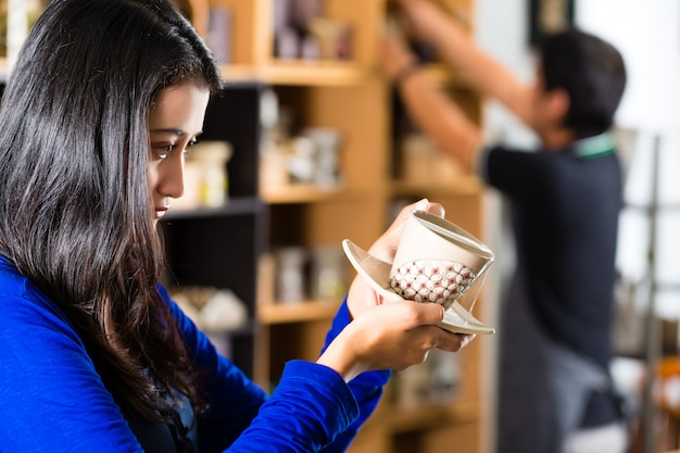 Cliente che tiene una tazza in un negozio di articoli da regalo