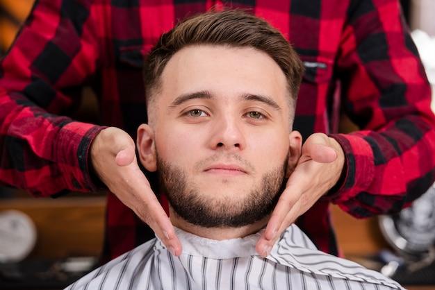 Cliente del primo piano con la sua barba sul punto