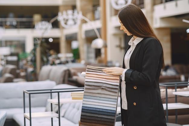 Cliente della donna che cerca bello tessuto nel negozio dei drappi