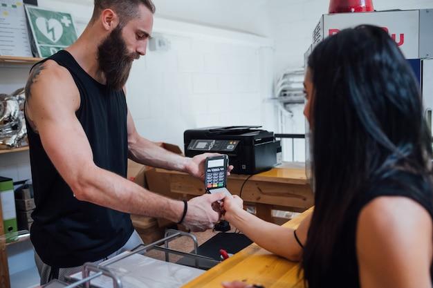 Cliente della donna che paga con la carta di credito facendo uso del terminale di posizione