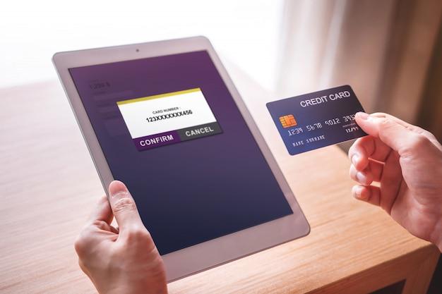 Cliente della giovane donna che usando la carta di credito e la compressa al pagamento online