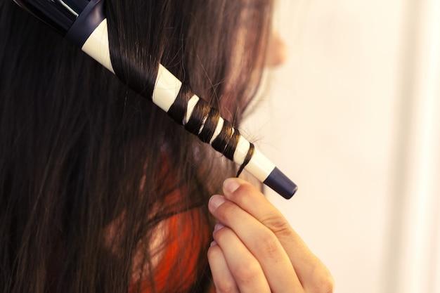 Cliente di arricciatura dei capelli del parrucchiere nel salone di parrucchiere