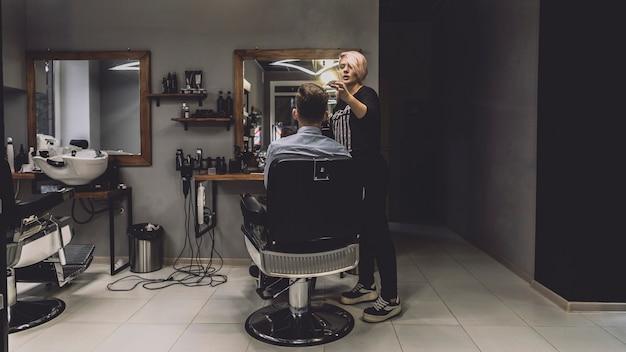 Cliente di styling della donna nel negozio di barbiere