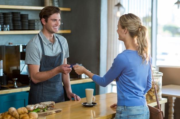Cliente felice che dà la carta di credito al cameriere