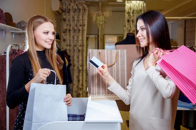 Cliente felice della donna che paga con la carta di credito nel negozio di modo