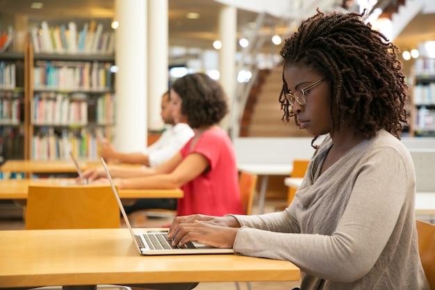 Cliente femminile concentrato che utilizza hotspot wi-fi pubblico nella biblioteca