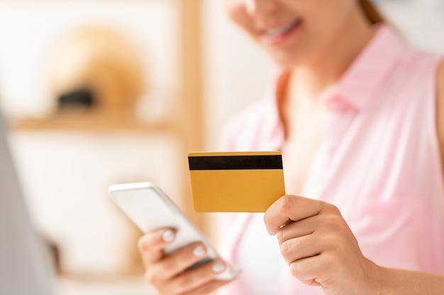 Cliente femminile contemporaneo che inserisce i dati dalla scheda di plastica nello smartphone mentre effettua l'ordine in linea