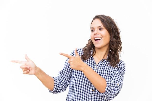 Cliente femminile emozionante felice che indica le dita