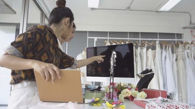 Cliente futuro della sposa che parla con il commerciante del negozio di nozze