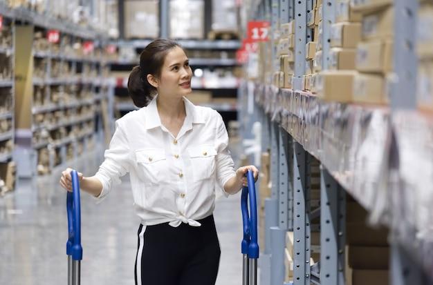 Cliente grazioso asiatico che cerca i prodotti nel magazzino del deposito.