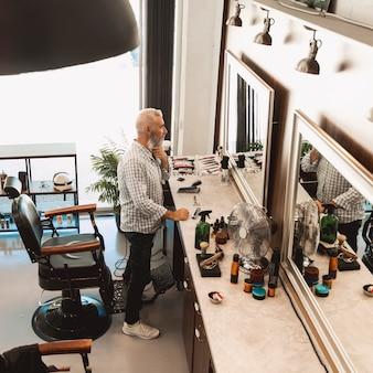 Cliente in piedi davanti allo specchio al barbiere