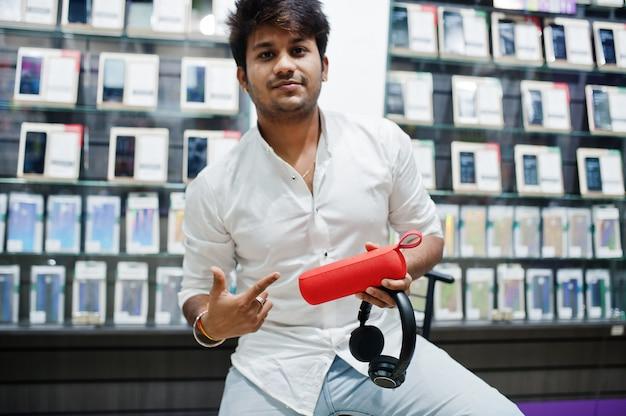 Cliente indiano dell'uomo al deposito del telefono cellulare con le cuffie e l'altoparlante senza fili che si siedono sulla sedia.