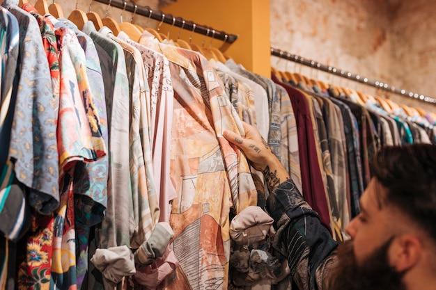 Cliente maschio che sceglie la camicia che appende sulla ferrovia nel negozio