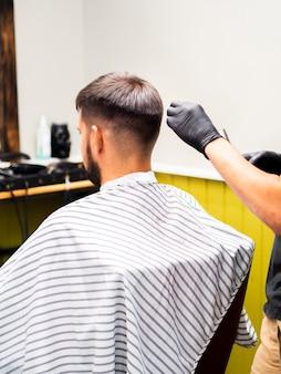 Cliente seduto su una sedia nel negozio di barbiere