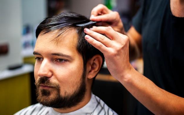 Cliente serio che si siede ancora per un taglio di capelli