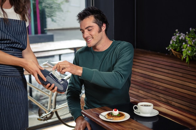 Cliente sorridente che paga ordine con lo smartphone