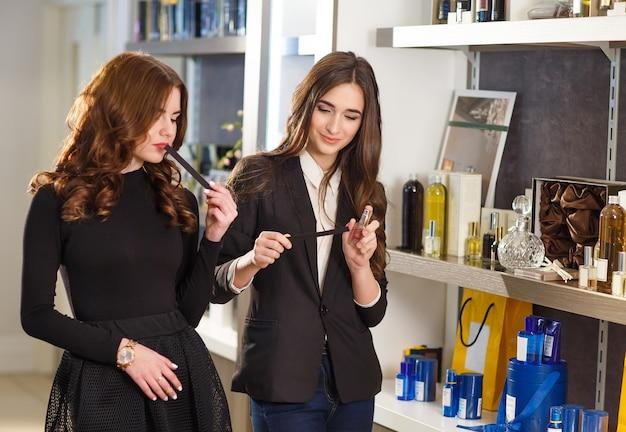 Cliente sorridente del servizio della commessa positiva dei giovani nel negozio di profumo.