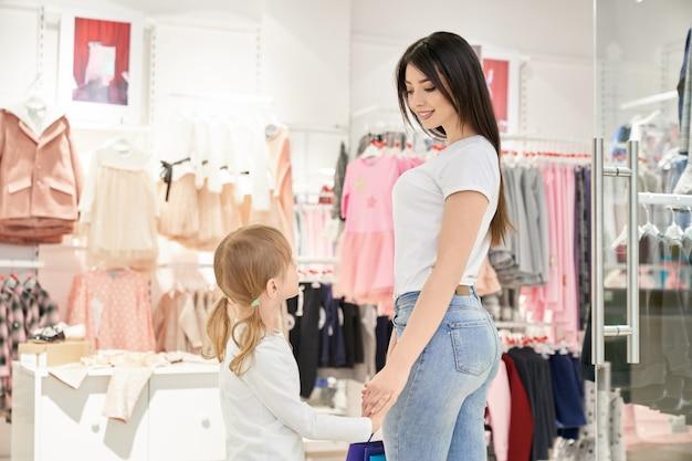 Clienti che scelgono abbigliamento per bambini alla moda in boutique.