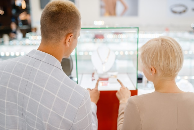 Clienti di sesso maschile e femminile alla ricerca di gioielli in gioielleria. uomo e donna che scelgono le fedi nuziali. futuri sposi in gioielleria