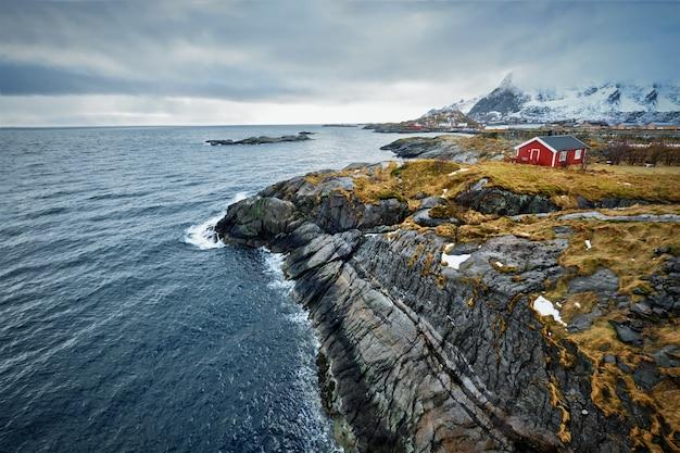 Clif con la tradizionale casa rorbu rossa sulle isole lofoten, norvegia