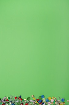 Clip e bottoni di cucito su fondo verde, vista superiore