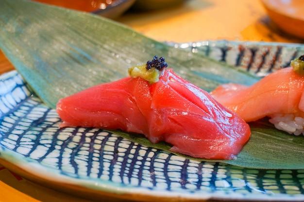 Close up akami (tonno rosso) sushi servito a mano con wasabi sott'aceto. pasto di lusso giapponese.
