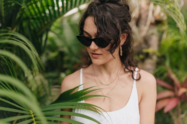 Close up al di fuori del ritratto di adorabile ragazza felice con i capelli ricci biondi indossando occhiali gialli moderni ed eleganti che giocano con i capelli e guardando verso il basso sulla parete delle piante verdi