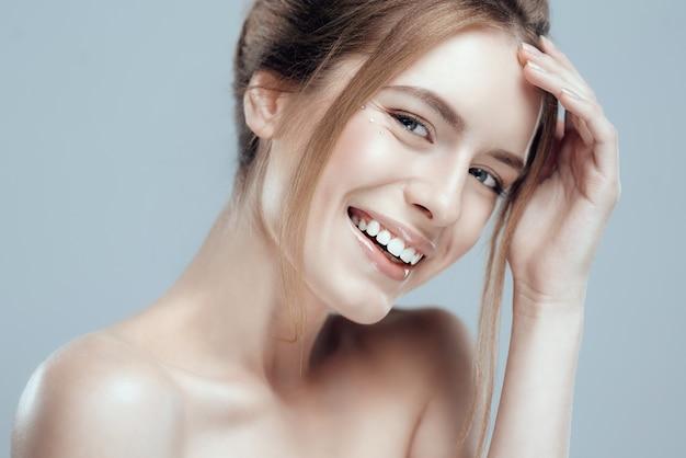 Close-up bella giovane donna con la pelle pulita fresca.