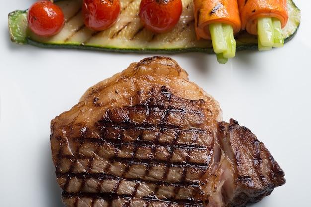 Close up bistecca di manzo hida con pomodoro grigliato, carota, cetriolo e asparagi
