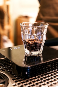 Close-up chicchi di caffè all'interno del bicchierino sulla bilancia digitale.