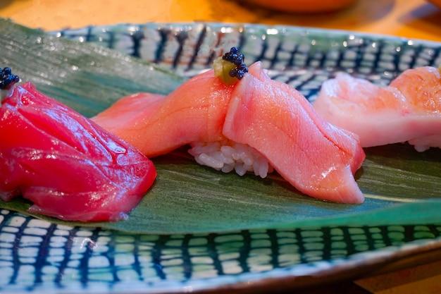Close up chutoro (tonno rosso) sushi servito a mano con wasabi sott'aceto. pasto di lusso giapponese.