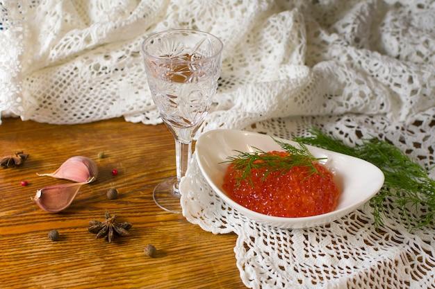 Close up composizione caviale rosso con vetro sfaccettato di vodka, ciotola bianca con caviale rosso e aneto sul vecchio tavolo di legno. cibo salutare. antipasto di pesce