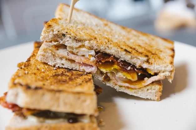 Close up croccante bacon ripieno di pane tostato francese con uovo fritto.