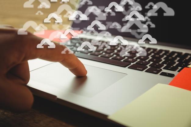Close-up del computer portatile con le icone di upload