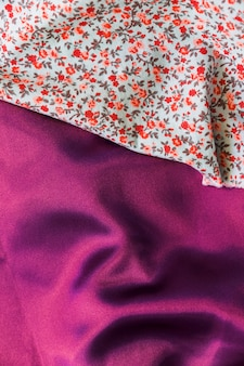 Close-up del tessile motivo floreale sul panno viola pianura