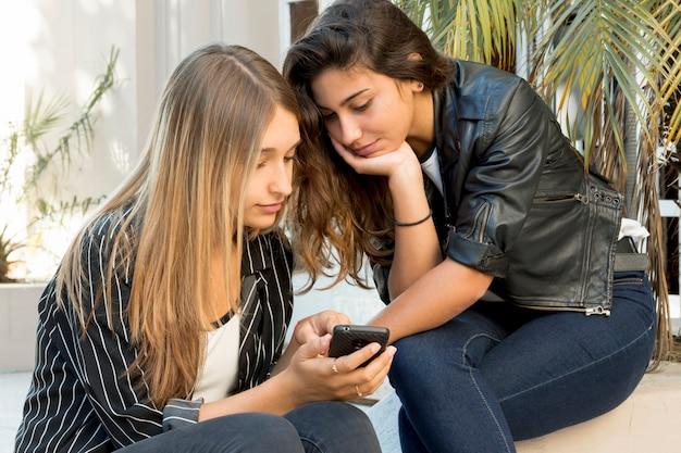 Close-up della bella ragazza adolescente che mostra cellulare al suo amico