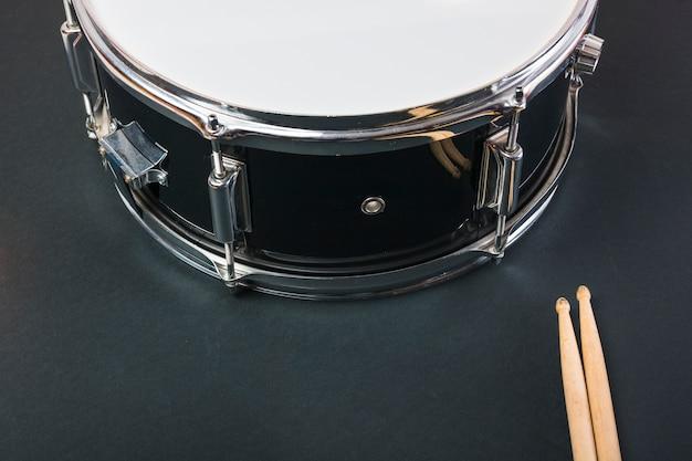 Close-up di bacchette di legno e tamburo su sfondo nero