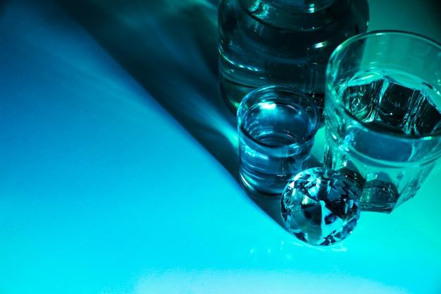 Close-up di bicchieri d'acqua e bottiglia con diamante su sfondo blu brillante