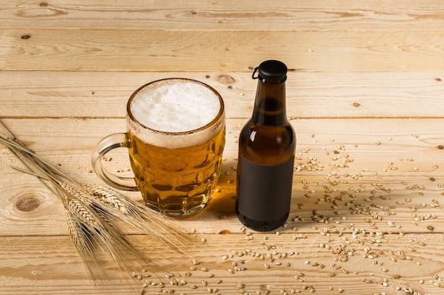 Close-up di birra in vetro e bottiglia con spighe di grano su fondo in legno