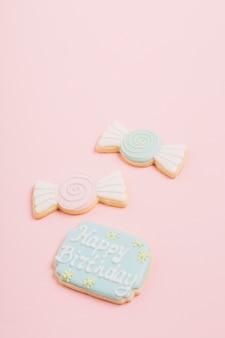 Close-up di biscotti con testo di buon compleanno su sfondo rosa