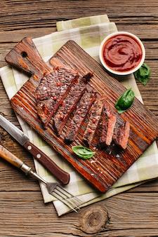 Close-up di bistecca fritta con salsa sul tavolo di legno