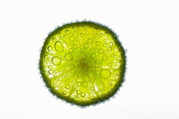Close-up di bolle d'aria che coprono fetta di calce succosa galleggianti in acqua