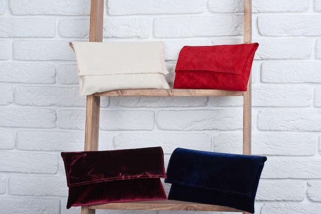 Close-up di borse da donna alla moda di rosso, bianco, blu e bordeaux, posa sul muro bianco.