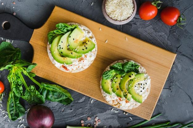 Close-up di cibo fresco delizioso sul tagliere con verdure fresche intorno