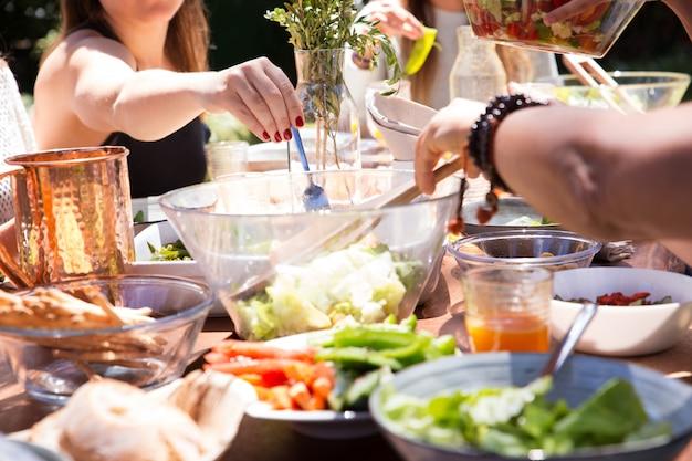 Close-up di ciotole e piatti con cibo e mano femminile con forchetta