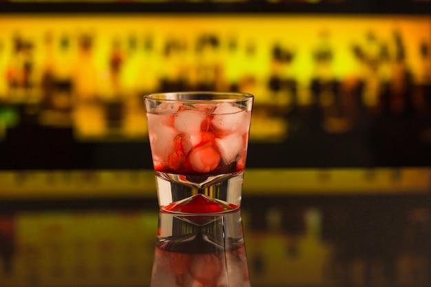 Close-up di cocktail con cubetti di ghiaccio al bancone del bar