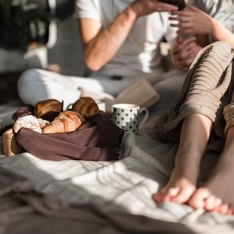 Close-up di coppia avendo croissant e caffè a colazione
